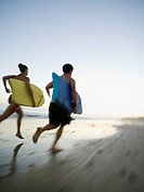 Multi-ethnic couple running with surfboards