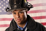 Hispanic male firefighter in front of American flag (thumbnail)
