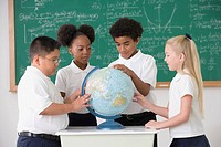 Multi-ethnic children looking at classroom globe