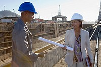 African American businesswoman and construction worker with blueprints