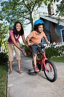 Mother teaching boy to ride bicycle