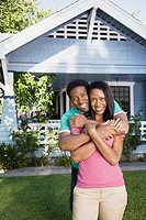 Smiling couple embracing in front of house