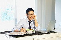 Asian businessman eating breakfast