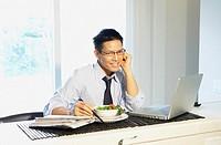 Asian businessman eating breakfast