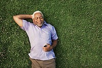 Senior man lying down on grass