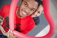African couple holding heart-shaped balloon
