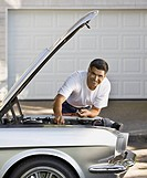 Hispanic man working under hood of car (thumbnail)