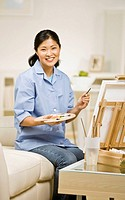 Asian woman painting at easel