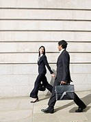 Multi-ethnic businesspeople walking on sidewalk