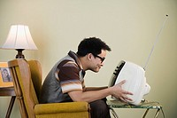 Nerdy Asian man holding television in front of face