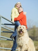 Multi-ethnic couple hugging next to dog