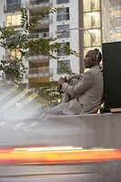 Businessman wearing headphones sitting outside