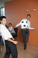 Businesspeople playing soccer inside