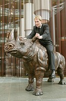 Man riding statue of rhino