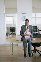 Businessman sitting with his baby