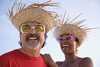 Multi-ethnic couple wearing straw hats