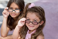 Hispanic sisters wearing eyeglasses