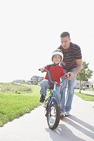 Father helping son ride bike