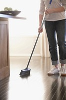Woman sweeping hardwood floors
