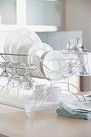 Plates, glasses, and eating utensils drying on dish rack