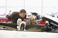 Father and son looking at car