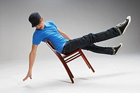 Playful young man balancing himself on a chair