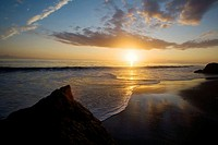 The sunset sets as clouds relect in the surf on a beach In Malibu, California, USA.
