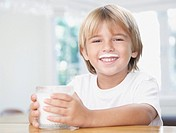 Young boy in kitchen with glass of milk