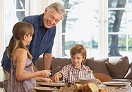 Man and two kids in dining room setting table