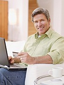 Man in living room with laptop and credit card