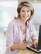 Woman in kitchen with laptop and credit card