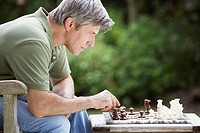 Man outdoors playing chess