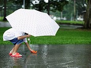 Young girl outdoors in rain playing with paper boat