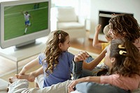 Family in living room watching sports on television