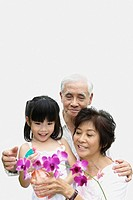 Couple and young girl indoors watering flower