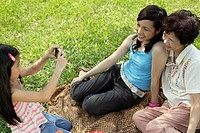 Young girl taking picture with digital camera of two women outdoors