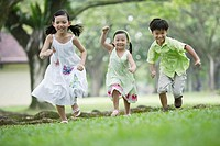 Three young kids outdoors at park running