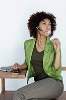 Businesswoman wearing headset and blowing bubble