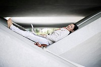 Businesswoman lying in structure with laptop
