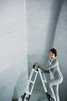Businesswoman in structure on ladder
