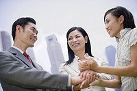 Three businesspeople outdoors holding hands in circle