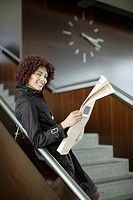 Businesswoman on staircase with newspaper