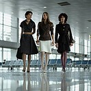 Three businesswomen walking through airport