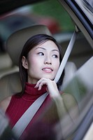 Businesswoman in car looking out window