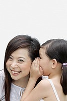 Young girl indoors whispering in woman's ear (thumbnail)