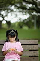 Young girl outdoors on bench with video game