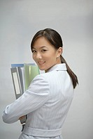 Businesswoman indoors holding binders