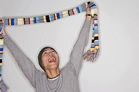 Man indoors holding up scarf laughing