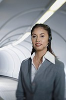 Businesswoman in corridor wearing headset