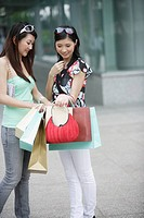 Two women outdoors looking in shopping bags